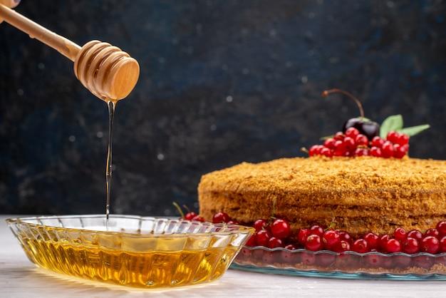 Круглый медовый торт, вкусный и запеченный с красной клюквой и медом на сером письменном столе, фото