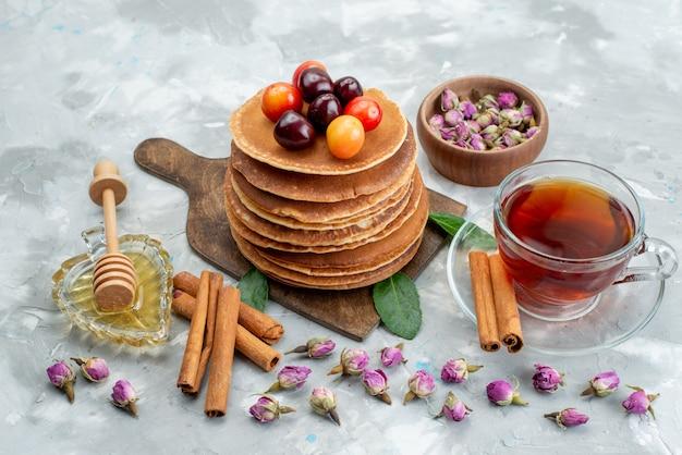 Вид спереди круглые блины, испеченные и вкусные с вишневым чаем на светлом письменном торте, фруктовая выпечка