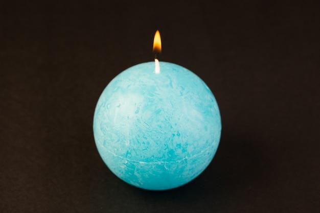 Вид спереди круглой формы свечей освещения синего цвета рассчитанных на темном фоне ярким огненным украшением
