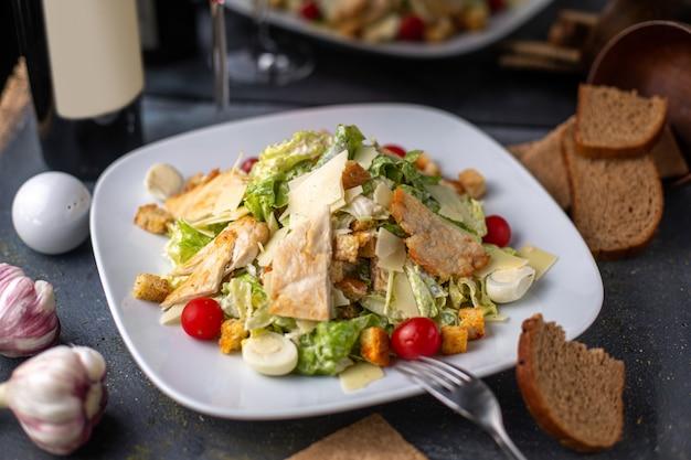 灰色の机のディナー料理に赤ワインのポテトチップスと白い皿に野菜の野菜を塩漬けにしたペッパーとスライスしたチキンの正面図