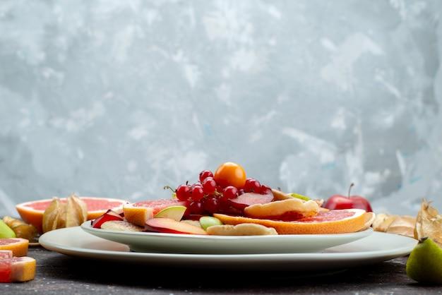Вид спереди нарезанные свежие фрукты спелые и спелые внутри белой тарелки на деревянном столе цвет фруктов еда цитрусовые