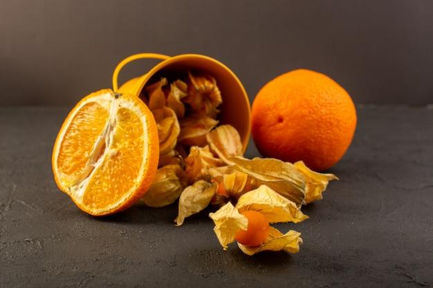 グレーに広がる皮をむいたオレンジの丸い果物とオレンジをスライスした正面図