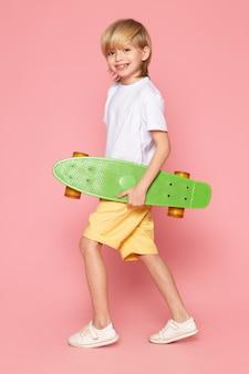 Вид спереди улыбающегося белокурого мальчика в белой футболке и желтых джинсах с зеленым скейтбордом на розовом пространстве