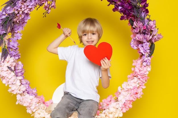 Вид спереди улыбающегося белокурого мальчика в белой футболке, держащего сердечко, сидящего на цветочной подставке на желтом полу