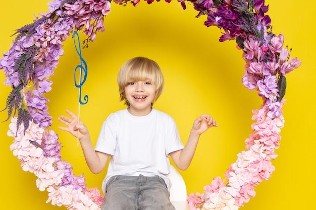 Вид спереди улыбающегося белокурого мальчика в белой футболке, сидящего на цветочной подставке на желтом столе
