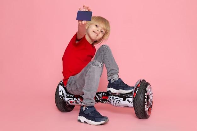 ピンクのスペースでセグウェイに座っている紫色のカードを示す赤いtシャツで正面笑顔の少年