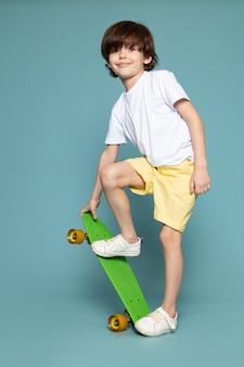 Вид спереди улыбающегося милого малыша на зеленом скейтборде в белой футболке и оранжевых шортах на голубом пространстве