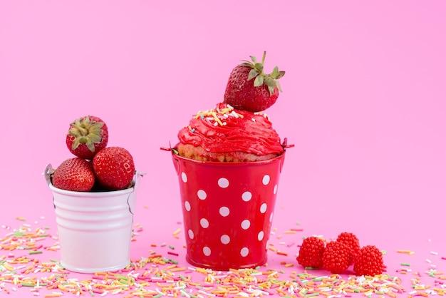 Клубничный торт, вид спереди внутри красной корзины вместе со свежей красной клубникой на розовом столе, бисквитный торт, кондитерский сахар