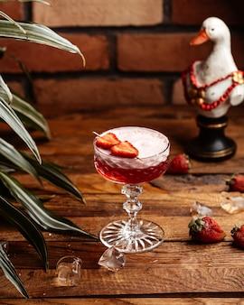 Клубничный коктейль, вид спереди, со свежей красной клубникой на столе, коктейль, сок, фрукты