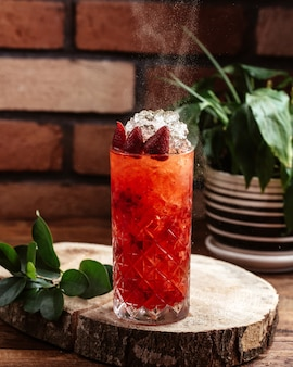 Клубничный коктейль с кубиками льда на коричневом деревянном столе, вид спереди, фруктовый коктейль jucie