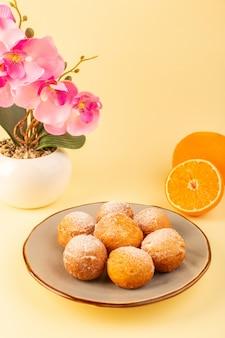 正面の砂糖粉ケーキ、丸いプラットフォーム内の甘い焼きたてのおいしい小さなケーキ、花、スライスしたオレンジ、クリーム色の背景のベーカリーの甘いビスケット
