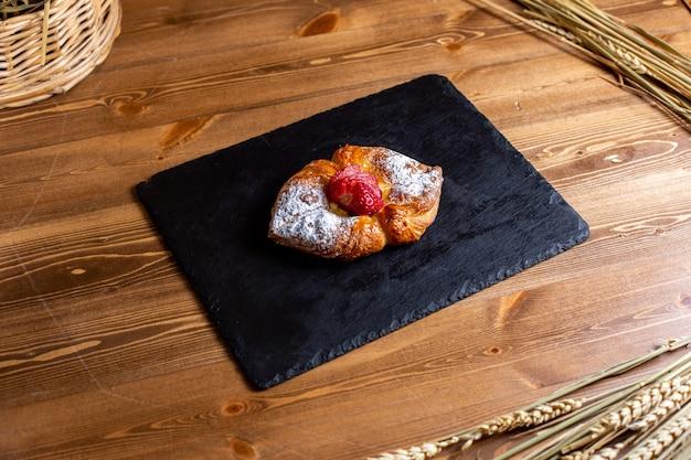 Вид спереди сладкий бублик с сахарной пудрой на черной ткани вкуснятина, изолированные на коричневом столе сахарное печенье