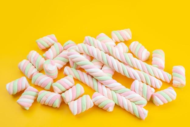 黄色の机、キャンディーシュガー甘い色に分離された正面甘いマシュマロ