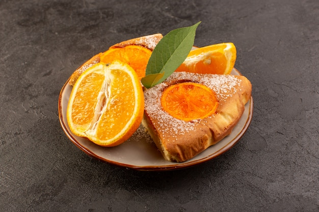 Вид спереди сладкий апельсиновый пирог сладкие вкусные кусочки пирога вместе с нарезанным апельсином внутри круглой пластины на сером фоне печенье сладкий сахар