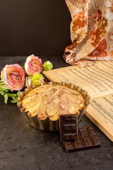 Вид спереди сладкий круглый торт вкусный вкусный внутри кекса, а также шоколадные батончики цветы и тетрадь на сером фоне печенье сахарное печенье