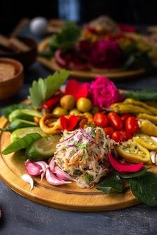 茶色の木製の机の上にスライスした正面野菜とキュウリの丸ごとレタス、灰色の机の上にあるパンのローフビタミン植物