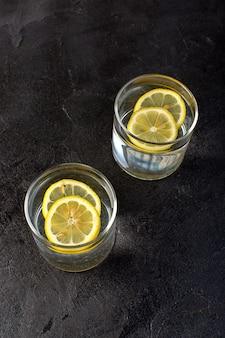 Вид спереди воды с лимонным напитком с нарезанными лимонами внутри прозрачных стаканов на темноте