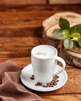 Вид спереди белая пустая чашка с коричневыми кофейными семечками на коричневом деревянном столе семя кофейной чашки
