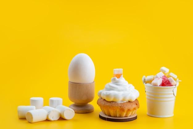 正面の白いマシュマロと黄色の机の上のケーキとキャンディー、砂糖菓子の甘いビスケット色