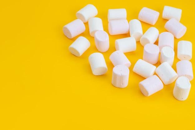 正面の白いマシュマロ黄色の机の上においしいお菓子、砂糖菓子キャンディー色