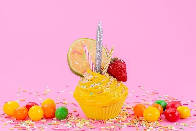 ピンクの机の上のカラフルなキャンディーと一緒に正面の黄色いケーキ、色の甘い砂糖