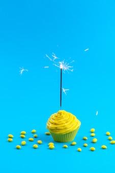 Желтый торт, вид спереди, вкусный с конфетами на синем столе, торт бисквитного цвета