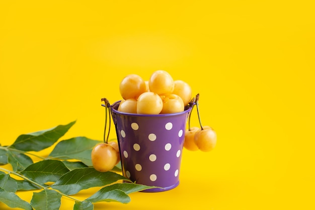 黄色の机の上の紫色のバスケットの中の黄色のさくらんぼのまろやかでジューシーな正面、果物の夏の色