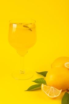 Вид спереди желтые свежие лимоны свежие спелые целые и нарезанные вместе с зелеными листьями лимонного напитка фрукты, изолированные на желтом фоне цвета цитрусовых фруктов