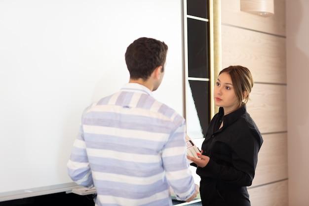 Вид спереди молодая привлекательная деловая женщина в черной рубашке вместе с молодым человеком, обсуждающим графики на столе, в то время как молодая леди представляет свою работу, читая документ по созданию рабочих мест