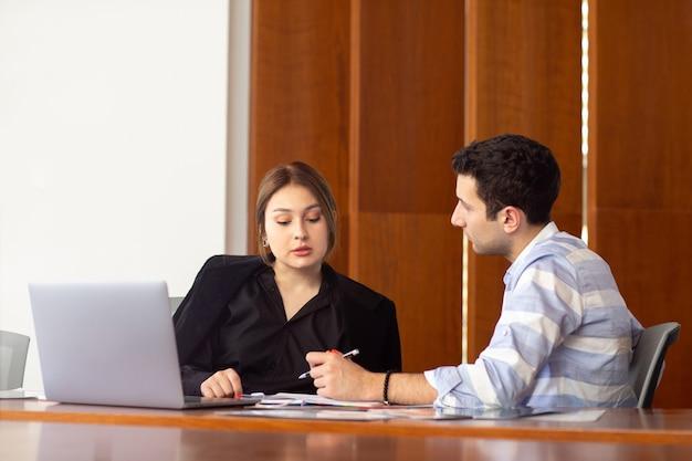 Вид спереди молодая привлекательная деловая женщина в черной рубашке и черной куртке вместе с молодым человеком, обсуждающим рабочие вопросы внутри ее конторской работы