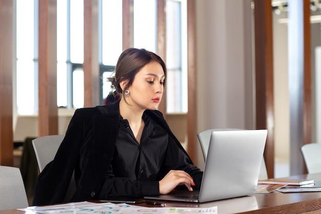 正面の若い魅力的な女性実業家彼女の銀色のラップトップを使用して彼女のオフィスの仕事の仕事の建物の中で作業している黒いシャツの黒いジャケット