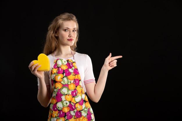 黒の背景に黄色のハートの形を保持しているカラフルなケープの正面若い魅力的な女の子愛笑顔陽性