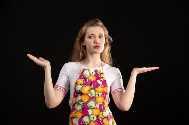 Вид спереди молодая привлекательная девушка в красочной накидке показывает недовольные признаки на черном фоне уборки домохозяйки