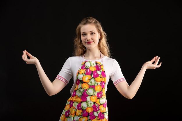 Вид спереди молодая привлекательная девушка в красочной накидке, показывая знаки своими руками, улыбаясь счастливым на черном фоне уборка домохозяйка
