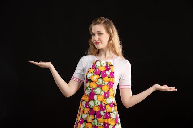 Вид спереди молодая привлекательная девушка в красочной накидке улыбается, показывая рукой знаки на черном фоне уборки домохозяйки