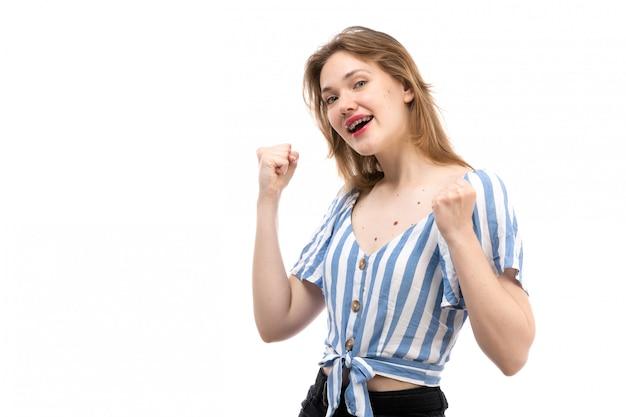 Вид спереди молодой привлекательной девушки в полосатой сине-белой футболке в черных джинсах, позирующей наполовину улыбаясь на белом