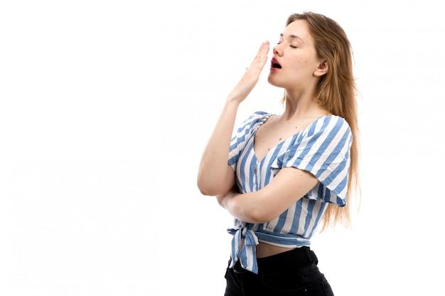 Вид спереди молодой привлекательной девушки в полосатой сине-белой футболке в черных джинсах, чихающих на белом