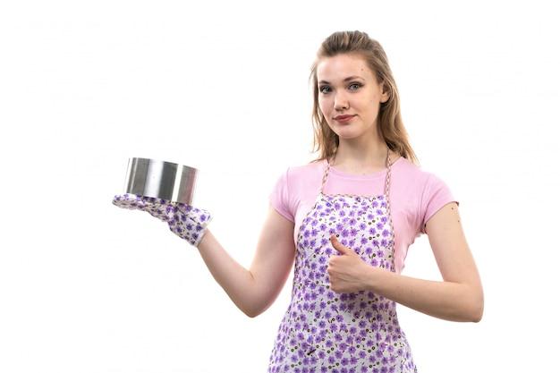 Вид спереди молодой привлекательной домохозяйки в розовой рубашке разноцветного плаща позирует улыбающегося, держащего круглую металлическую миску на белом фоне кухню кухонного женского пола
