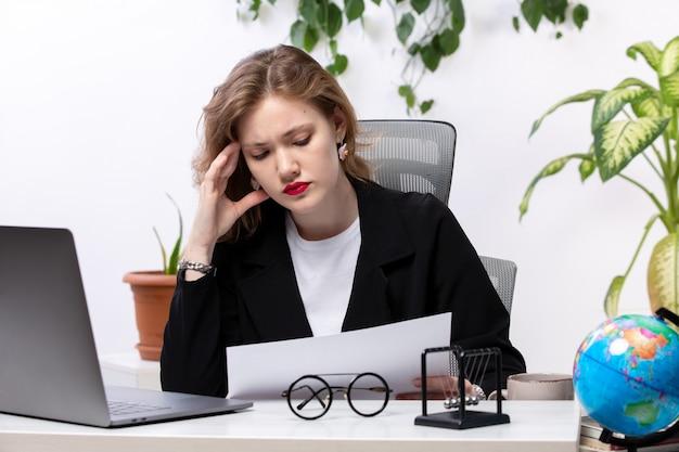 Вид спереди молодой привлекательной леди в черном пиджаке и белой рубашке перед столом, работающим с ноутбуком, документами, работающими бизнес-технологиями