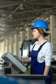 Вид спереди молодая привлекательная дама в голубом строительном костюме и шлем контролирует машины в ангаре, работающем в дневное время.