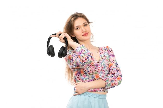 カラフルな花の正面の若い魅力的な女性のデザインのシャツと白に黒のイヤホンを保持している青いスカート