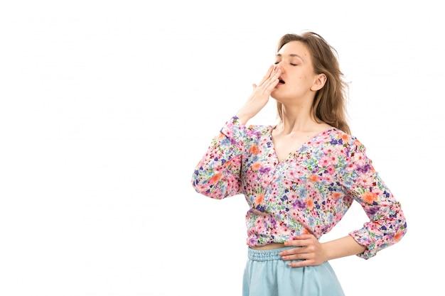 Вид спереди молодая привлекательная дама в разноцветной рубашке с цветочным рисунком и синей юбке позирует чихая на белом