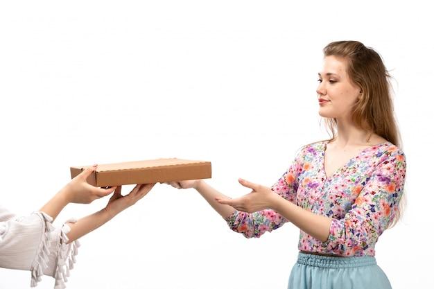 カラフルな花の正面の若い魅力的な女性がシャツと白に茶色のパッケージを取る青いスカートをデザイン