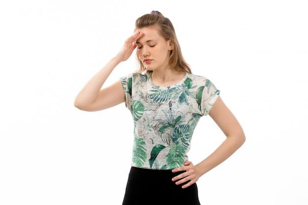 デザインされたシャツと白の頭痛に苦しんでいる黒のスカートの正面の若い魅力的な女性