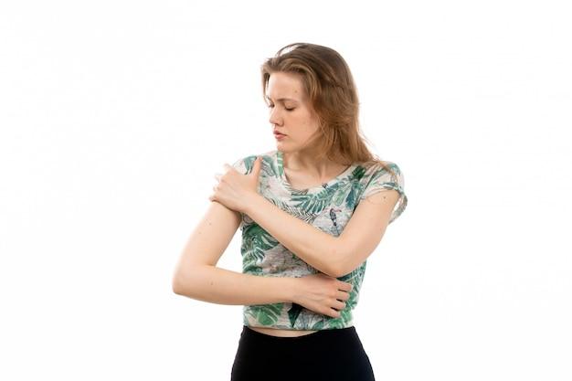 디자인 된 셔츠와 흰색에 팔 통증으로 고통받는 검은 바지에 전면보기 젊은 매력적인 아가씨
