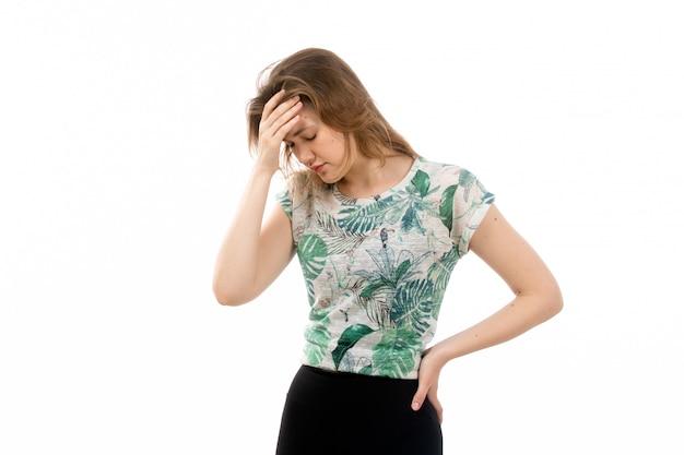 設計されたシャツと白で頭痛に苦しんでいる黒のズボンの正面の若い魅力的な女性