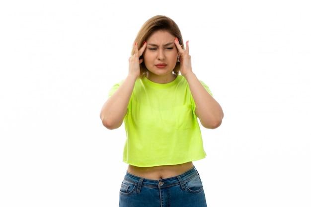緑のシャツと白の頭痛に苦しんでいるブルージーンズの正面若い魅力的な女性