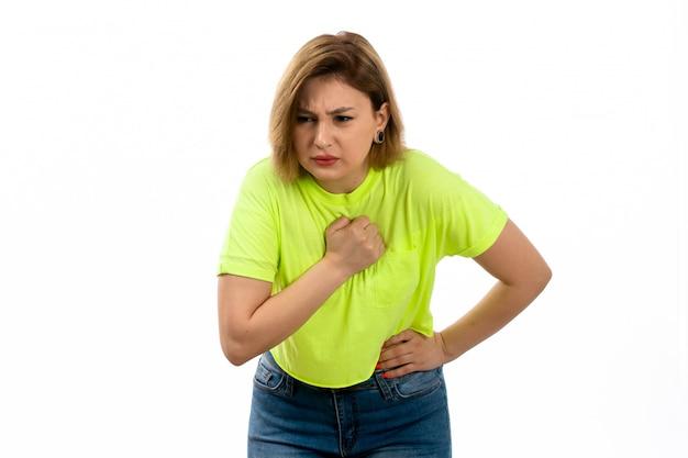 緑のシャツと白の腹痛に苦しんでいるブルージーンズの正面若い魅力的な女性