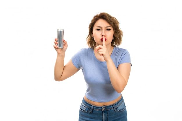 Вид спереди молодая привлекательная дама в серой футболке и синих джинсах с серебряной банкой показывает знак молчания на белом