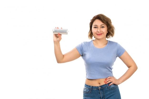 Вид спереди молодой привлекательной леди в серой футболке и синих джинсах с серебряной банкой, улыбающейся на белом